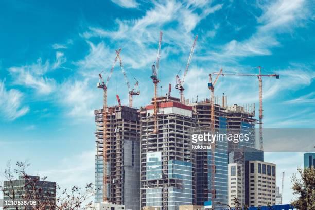 construction site against blue sky - 建物の骨組み ストックフォトと画像