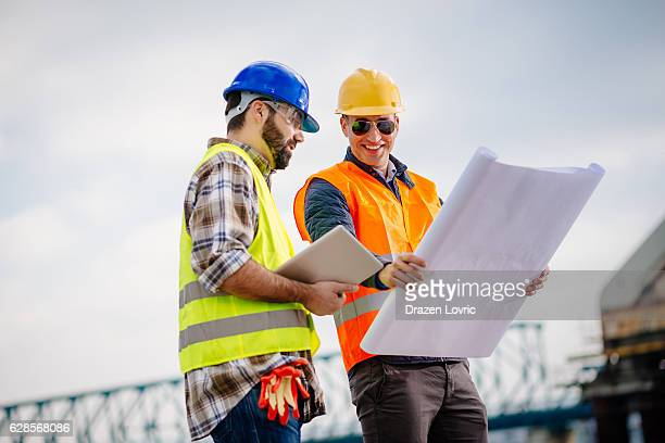 construction site and construction workers with blueprint - bridge built structure stock pictures, royalty-free photos & images
