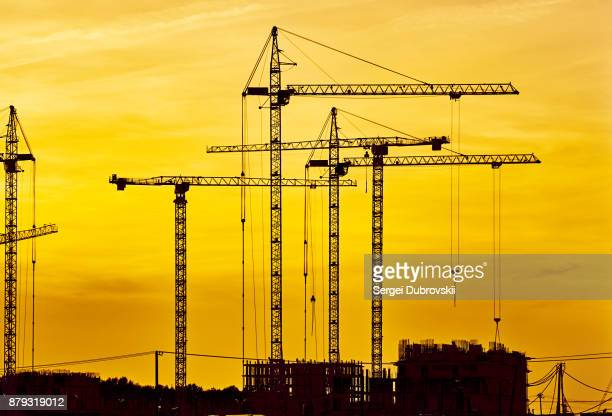 construction site at dusk evening yellow light, crane - crane stock pictures, royalty-free photos & images