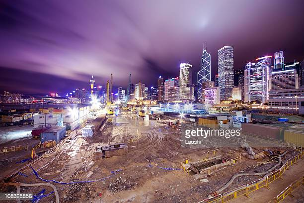 A construction site at night with a city skyline