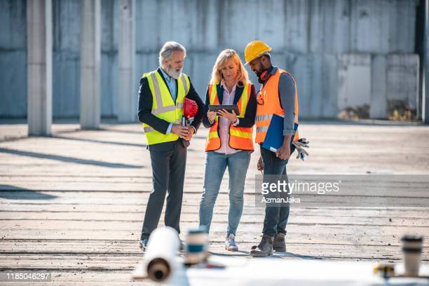 construction site development team checking digital tablet - construction industry stock pictures, royalty-free photos & images