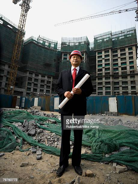 Construction site foreman with blueprints outdoors