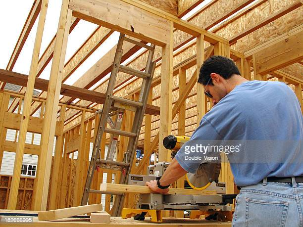 construction site: man with safety glasses uses miter saw - mitre stock pictures, royalty-free photos & images