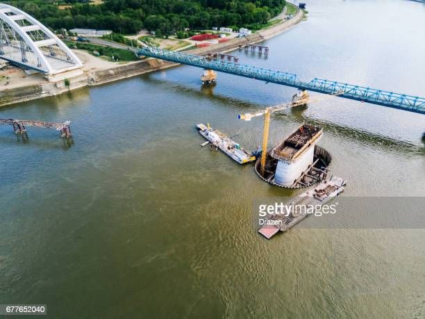 construction site of the bridge building on river danube - bridge built structure stock photos and pictures
