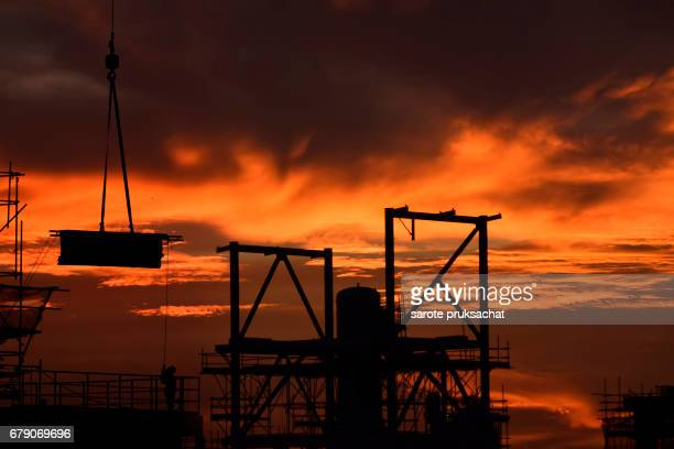 Construction site .Silhouette structural steel beam build large residential buildings at construction site .