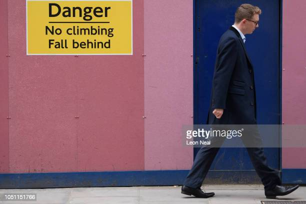 A construction site warning sign reading No Climbing Fall Behind is seen as commuters head to work a decade after the British Government paid...