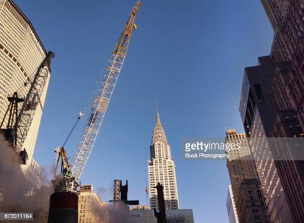 Construction site with tall cranes near Grand Central Terminal along East 42nd Street, with the Metlife Building and the Chrysler Building in the background. Midtown Manhattan, New York City