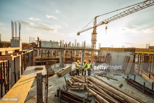 construction site with three engineers and crane on the top of new skyscraper - skyscraper stock pictures, royalty-free photos & images