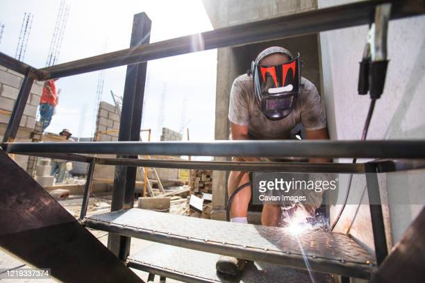 construction site worker welding staircase at building site. - in flames i the mask stock pictures, royalty-free photos & images