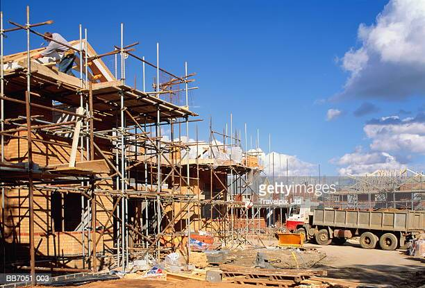 Construction site, workers building four-bedroom houses, England