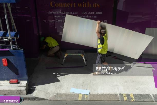 Construction site workman carries reflective metal sheeting on to the site of a development on Victoria Street in Westminster, on 30th July 2020, in...