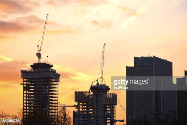 Construction sites are pictured at Canary Wharf as the sun sets, in London on November 17, 2017. Several banks and financial enterprises are...