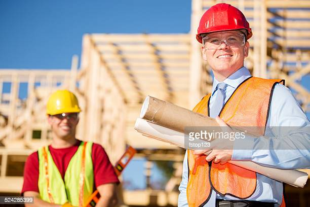 Construction supervisor carries blueprints at work site. Worker. Building.