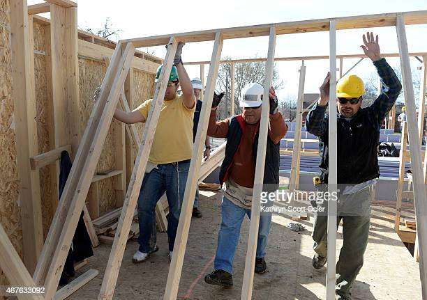 Construction supervisor Keith Faris right future homeowner Leo Hermosillo and volunteer Terry Williams work together to put framing in place Habitat...