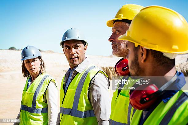 construction team discussing at quarry - ear protection stock pictures, royalty-free photos & images