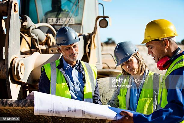 Construction team examining blueprint at quarry