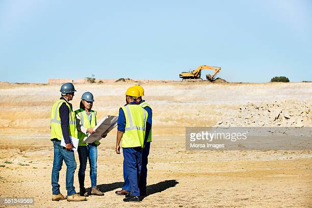 Construction team working on blueprint at quarry