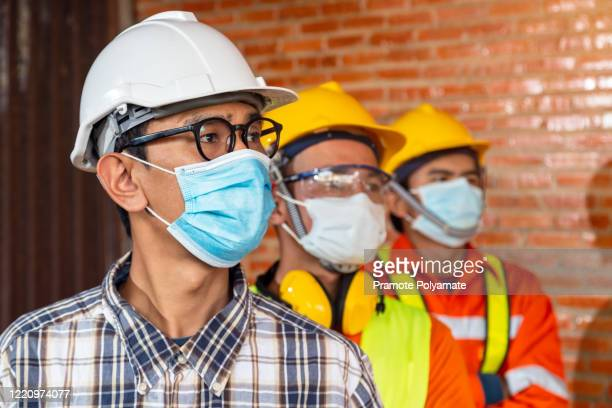 [construction teamwork ] team of construction engineers and three architects are ready to wear medical masks. corona or covid-19 wear masks during the design of construction. - thailand stock pictures, royalty-free photos & images