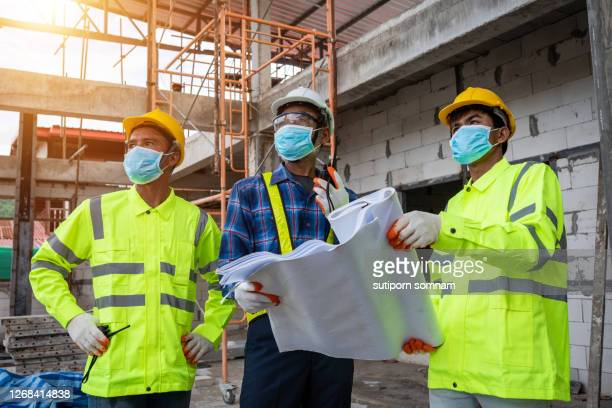 construction the engineering and worker with blueprint in  the construction site - construction industry stock pictures, royalty-free photos & images