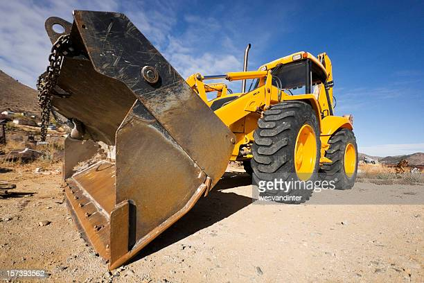 A construction vehicle with four wheels and front end loader