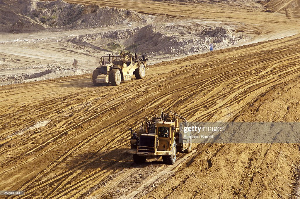 Construction Vehicles Driving on a Construction Site : Stock Photo