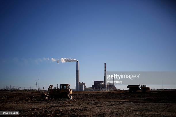 Construction vehicles operate as emissions rise from the Kentucky Utilities Co EW Brown generating station in Harrodsburg Kentucky US on Monday Oct...