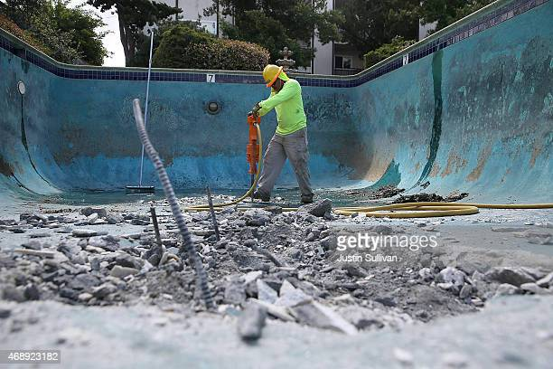 Construction worker Alex Hernandez uses a jackhammer to demolish a swimming pool at an apartment complex on April 8 2015 in Hayward California As...
