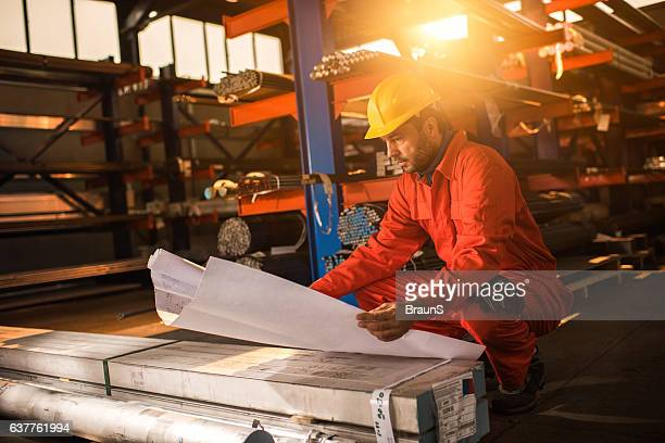Construction worker analyzing blueprints in industrial building.