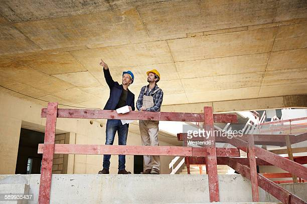 Construction worker and architect talking on construction site