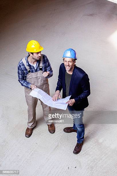 Construction worker and architect with plan talking on construction site