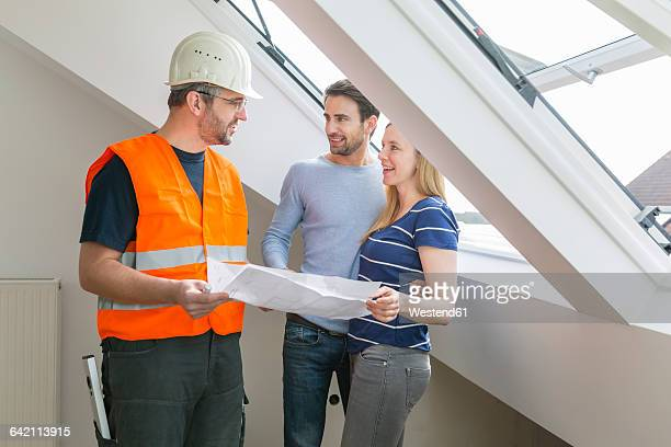 Construction worker and couple discussing rebuilding of their new home