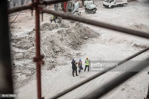 Construction worker and executives talking on construction site
