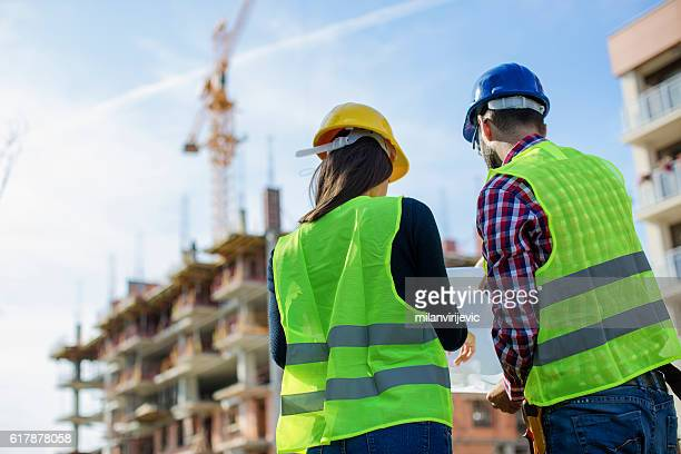 Construction worker and his manager checking the progress