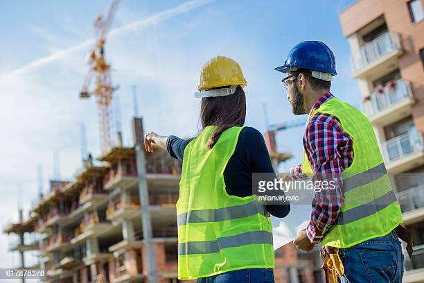 Construction worker and his manager looking at blueprints