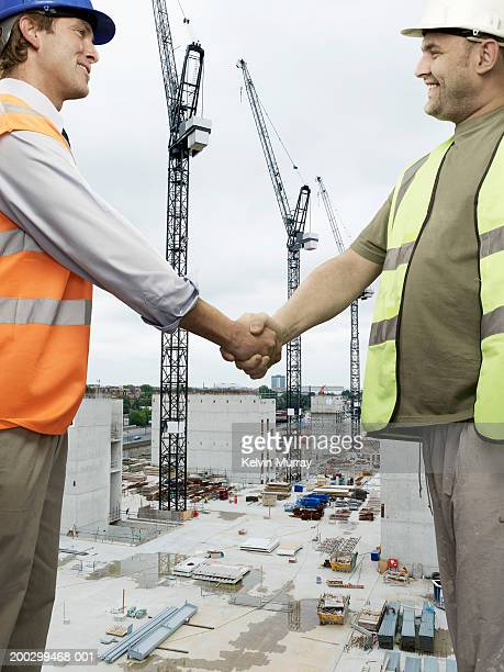 Construction worker and surveyor shaking hands on building site