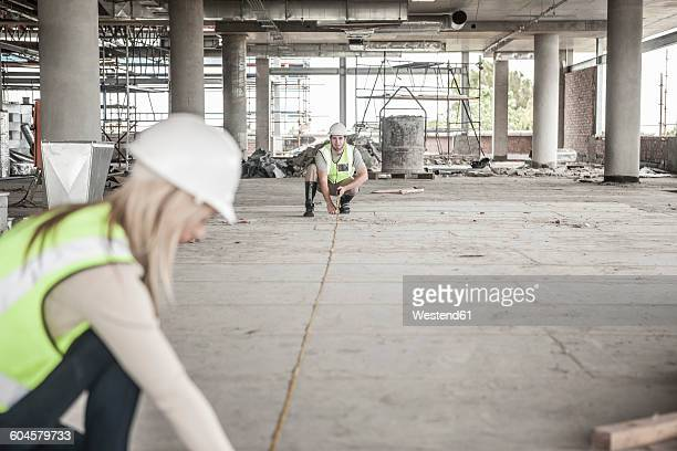 Construction worker and woman using tape measure in construction site