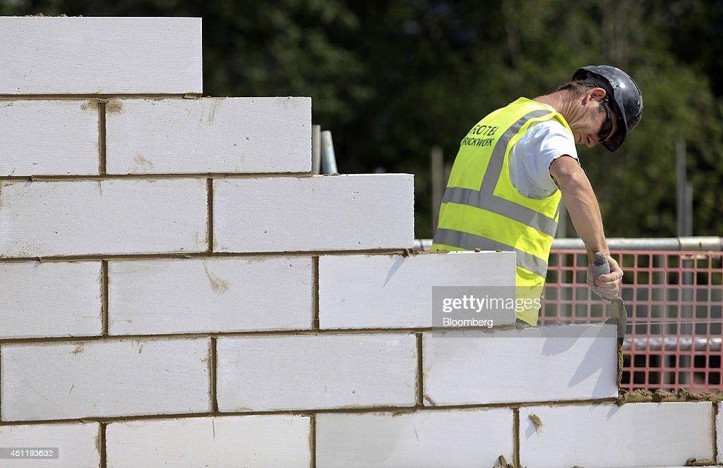 A Construction Worker Applies Mortar To The Breeze Block Bricks Of A New  Home Under Construction