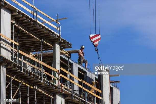 Construction worker beside a crane winch operating at a residential apartment construction site, on a plot of brownfield land in the Vysoany district...