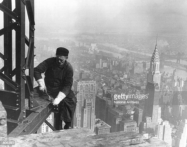 A construction worker does structural work with the Empire State Building in the background in New York City around 1930