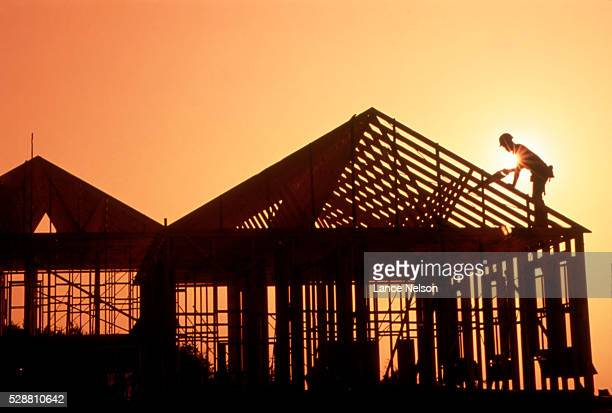 Construction worker building house at sunset