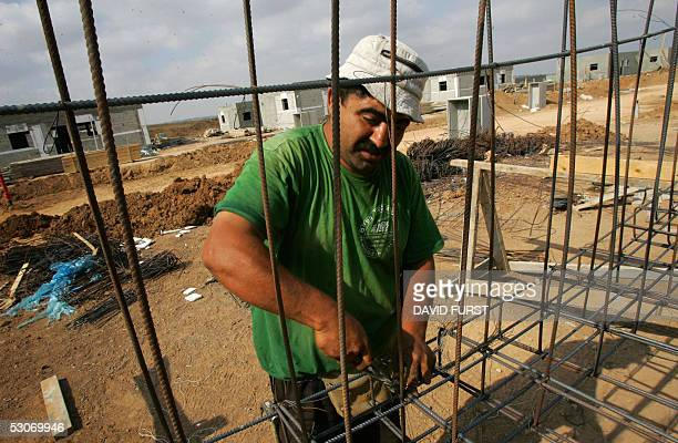 A construction worker builds a house meant for the relocation of Israeli settlers from the Gush Katif settlement bloc in advance of Israel's Gaza...
