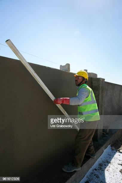 A construction worker builds a wall around the refugee camp Kabarto 2 in the district Semeel on April 23 2018 in DOHUK IRAQ The german goverment is...