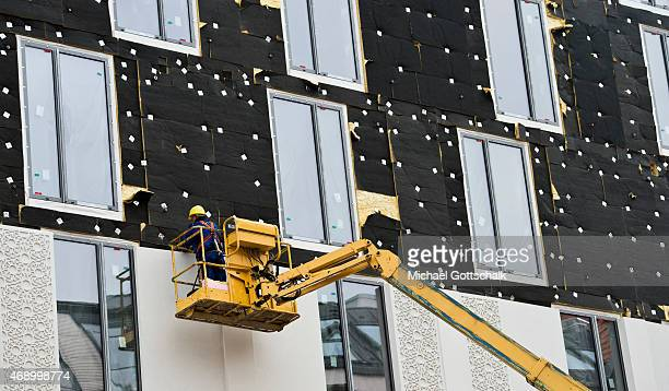 A construction worker builds thermal insulation at a facade on April 09 2015 in Berlin Germany