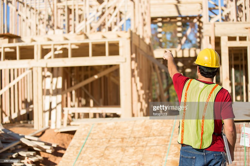 Construction worker busy working at job site. Framed building. Materials. : Stock Photo