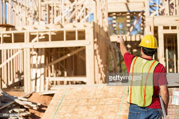 construction worker busy working at job site. framed building. materials. - real estate developer stock pictures, royalty-free photos & images