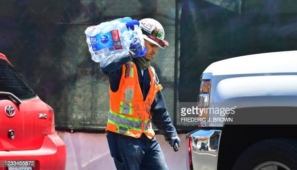 Construction worker carries a 24-pack of bottled water over his shoulder on June 14, 2021 in Los Angeles, where an early season heat wave is set to...