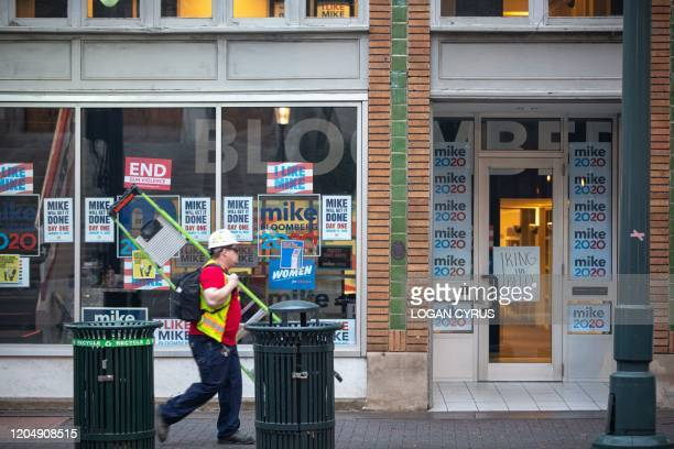 Construction worker carries a ladder as he walks past the Michael Bloomberg campaign office in uptown Charlotte during the North Carolina primary on...