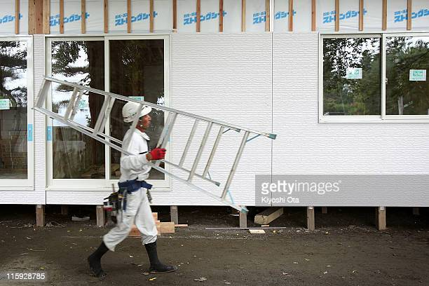 A construction worker carries a ladder as he works on temporary houses for evacuees who suffered from the March 11 earthquake and tsunami as seen on...