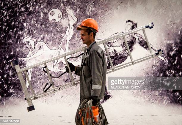 A construction worker carries a ladder by a picture depicting two football players at the Yekaterinburg Arena in Yekaterinburg on September 18 2017...