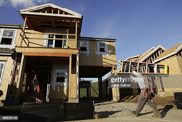 A construction worker carries a ladder in front of a new home under construction January 19 2006 in Dublin California The Commerce Department...